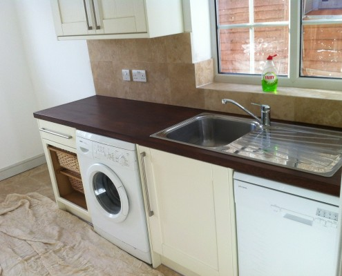 After image of the kitchen with the marble floor and wall tiles and stained oak worktop
